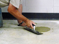 Repairing the cored holes in the concrete slab floor with fresh concrete and cleaning up the Stevens Point home.
