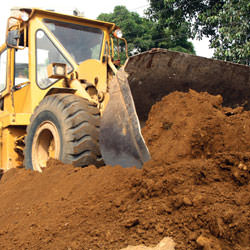 Construction equipment excavating soils during a foundation construction