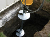 Installing a helical pier system in the earth around a foundation in Sheboygan