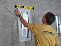 Positioning a wall plate cover on a foundation wall in Manitowoc.