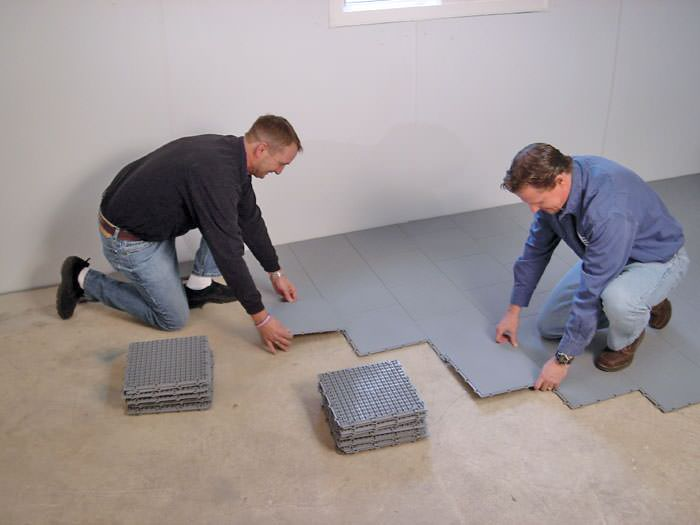 Contractors installing basement sub floor tiles and matting on a